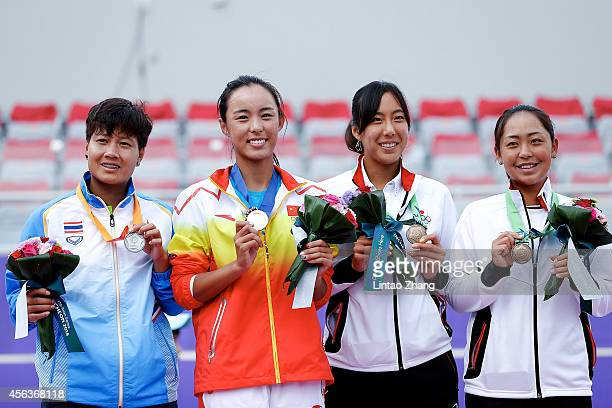 Silver medalists Luksika Kumkhum of Thailand gold medalists Wang Qiang of China and bronze medalists Eri Hozumi and Misa Eguchi of Japan celebrate...