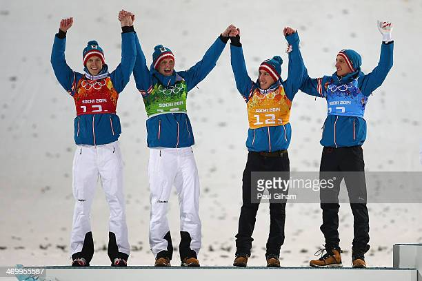 Silver medalists Michael Hayboeck Thomas Morgenstern Thomas Diethart and Gregor Schlierenzauer of Austria celebrate during the flower ceremony for...