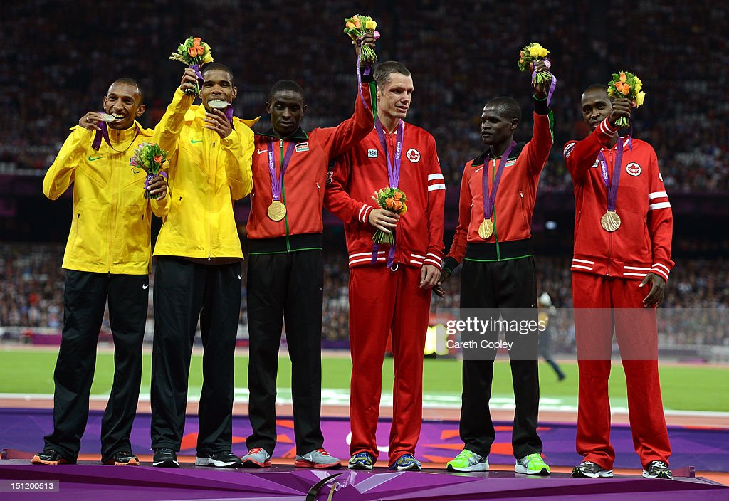 Silver medalists Odair Santos of Brazil and his guide Carlos Antonio dos Santos, Gold medalists Samwel Mushai Kimani of Kenya and his guide James Boit and bronze medalists Jason Joseph Dunkerley of Canada and his guide Josh Karanja pose on the podium during the medal ceremony for the Men's 1500m - T11 on day 5 of the London 2012 Paralympic Games at Olympic Stadium on September 3, 2012 in London, England.