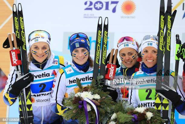 Silver medalists Stina Nilsson Ebba Andersson Charlotte Kalla and Anna Haag of Sweden celebrate during the flower ceremony for the Women's Cross...