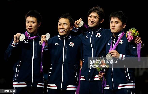 Silver medalists Suguru Awaji, Yuki Ota, Ryo Miyake and Kenta Chida of Japan celebrate on the podium during the medal ceremony after the Men's Foil...
