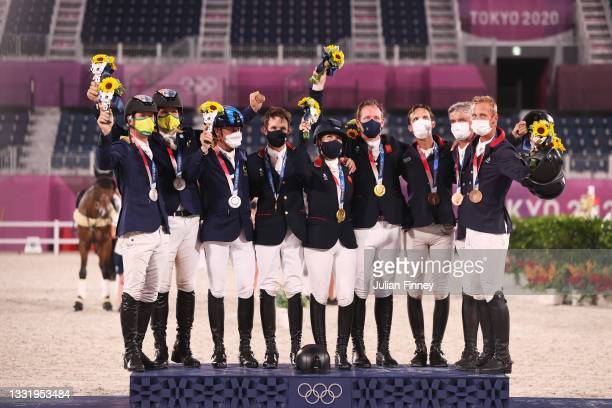 Silver medalists Team Australia, gold medalists Team Great Britain and bronze medalists Team France pose on the podium during the Eventing Jumping...