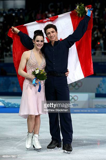 Silver medalists Tessa Virtue and Scott Moir of Canada celebrate during the flower ceremony for the Figure Skating Ice Dance on Day 10 of the Sochi...