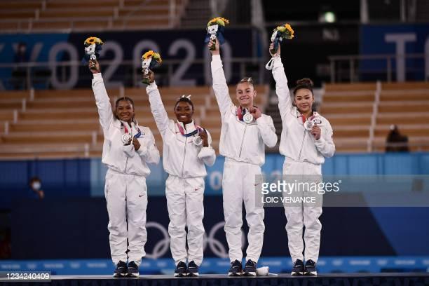 Silver medalists USA's Sunisa Lee, USA's Grace Mc Callum USA's Simone Biles and USA's Jordan Chiles wave on the podium of the artistic gymnastics...