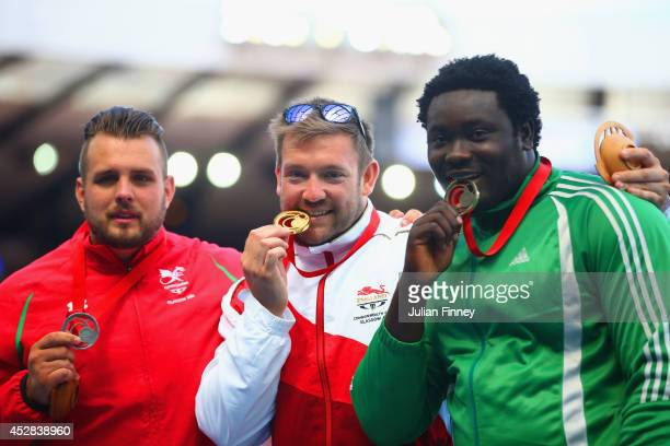 Silver medallist Aled Davies of Wales gold medallist Dan Greaves of England and bronze medallist Richard Okigbazi of Nigeria stand on the podium...