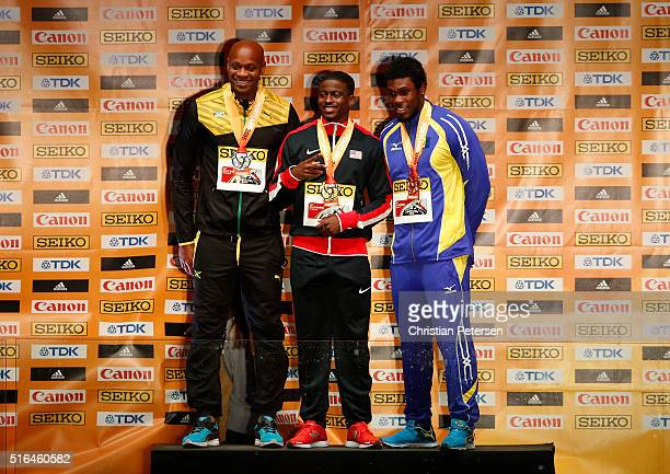 PORTLAND OR MARCH Silver medallist Asafa Powell of Jamaica gold medallist Trayvon Bromell of the United States and bronze medallist Ramon Gittens of...