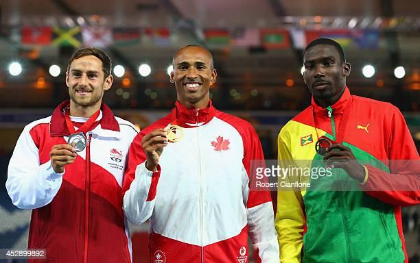 Silver medallist Ashley Bryant of England Gold medallist Damian Warner of Canada and bronze medallist Kurt Felix of Grenada pose on the podium during...