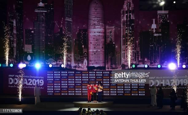 Silver medallist Bahrain's Rose Chelimo gold medallist Kenya's Ruth Chepngetich and bronze medallist Namibia's Helalia Johannes pose on the podium...
