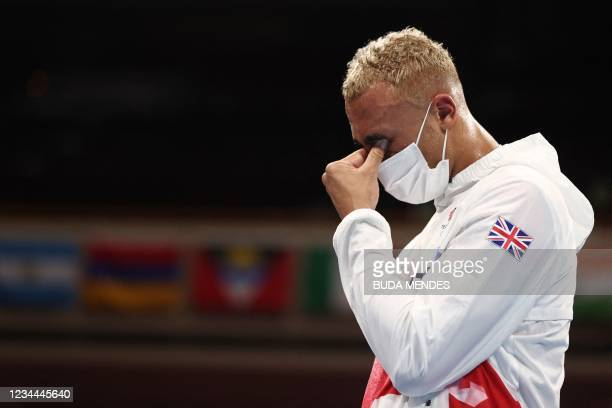 Silver medallist Britain's Benjamin Whittaker reacts on the podium after the men's light heavy boxing final bout during the Tokyo 2020 Olympic Games...