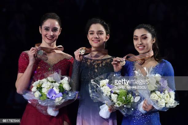 Silver medallist Canada's Kaetlyn Osmond Gold medallist Evgenia Medvedeva of Russia and Bronze medallist Canada's Gabrielle Daleman listen to the...