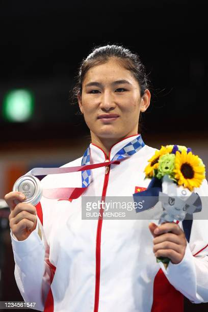 Silver medallist China's Li Qian celebrates on the podium during the victory ceremony for the women's middle boxing final bout during the Tokyo 2020...