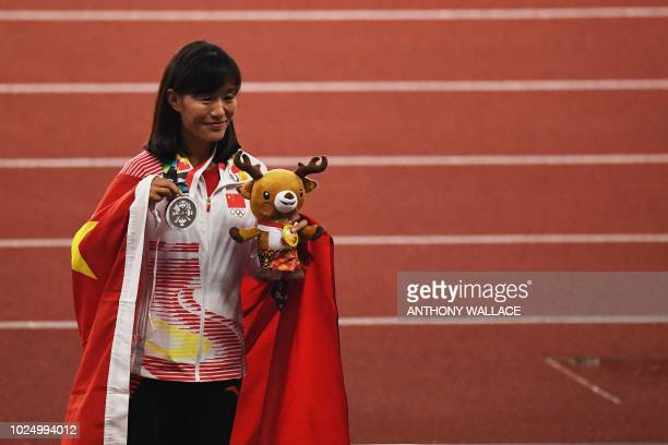Silver medallist China's Qieyang Shijie celebrates during the victory ceremony for the women's 20km race walk athletics event during the 2018 Asian...