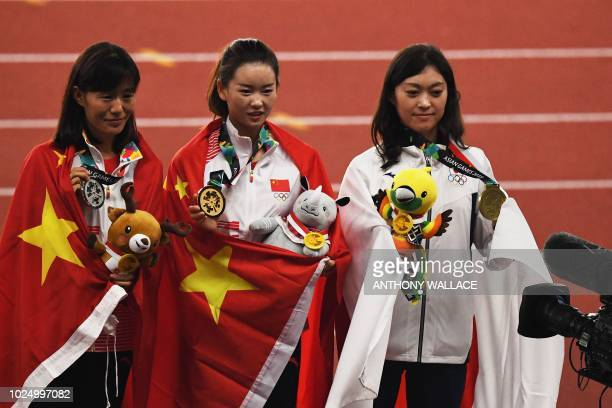 Silver medallist China's Qieyang Shijie gold medallist China's Yang Jiayu and bronze medallist Japan's Kumiko Okada celebrate during the victory...
