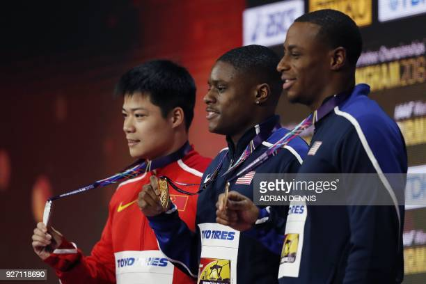 Silver medallist China's Su Bingtian gold medallist US athlete Christian Coleman and bronze medallist US athlete Ronnie Baker pose on the podium...
