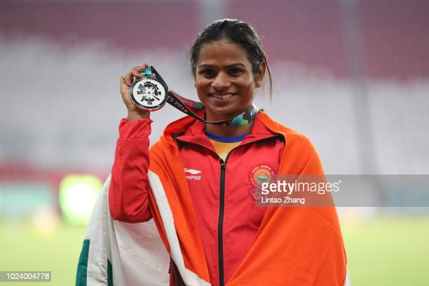 Silver medallist Dutee Chand of India poses on the podium during the awards ceremony for the Athletics Women's 100m final on day eight of the Asian...