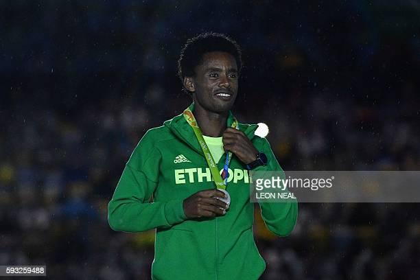 Silver medallist Ethiopia's Feyisa Lilesa poses on the podium for the Men's marathon athletics event during the closing ceremony of the Rio 2016...