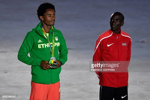 Silver medallist Ethiopia's Feyisa Lilesa poses on the podium of the men's marathon during the closing ceremony of the Rio 2016 Olympic Games at the...