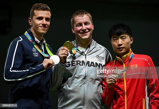 Silver medallist France's Jean Quiquampoix gold medal winner Germany's Christian Reitz and bronze medallist China's Li Yuehong stand on the podium...