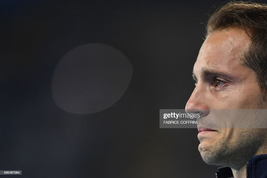 TOPSHOT - Silver medallist France's Renaud Lavillenie cries during the medal ceremony for the men's pole vault during the athletics event at the Rio 2016 Olympic Games at the Olympic Stadium in Rio de Janeiro on August 16, 2016. / AFP / FABRICE