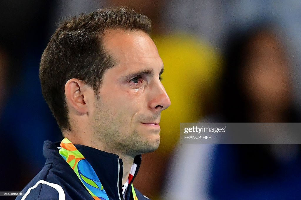 TOPSHOT - Silver medallist France's Renaud Lavillenie cries on the podium during the medal ceremony for the men's pole vault during the athletics event at the Rio 2016 Olympic Games at the Olympic Stadium in Rio de Janeiro on August 16, 2016. / AFP / FRANCK