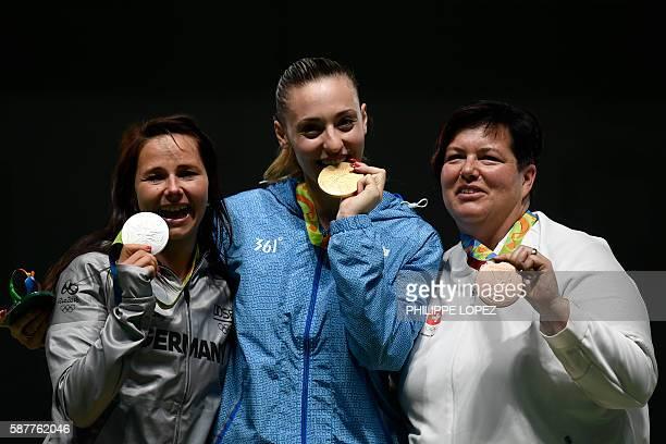 Silver medallist Germany's Monika Karsch gold medallist Greece's Anna Korakaki and bronze medallist Switzerland's Heidi Diethelm Gerber pose on the...
