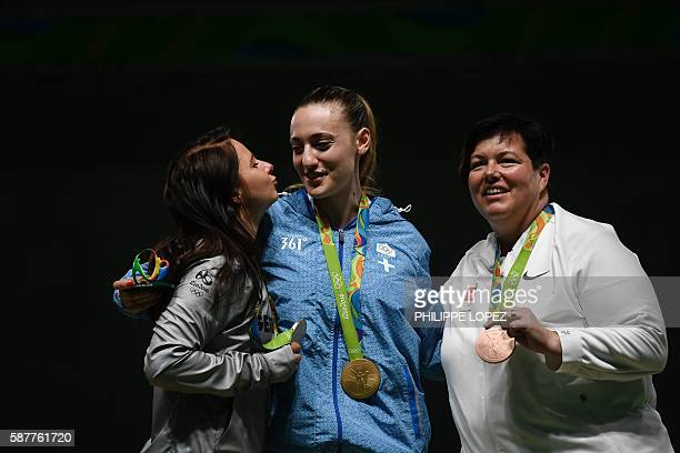 Silver medallist Germany's Monika Karsch kisses gold medallist Greece's Anna Korakaki as they pose with bronze medalist Switzerland's Heidi Diethelm...