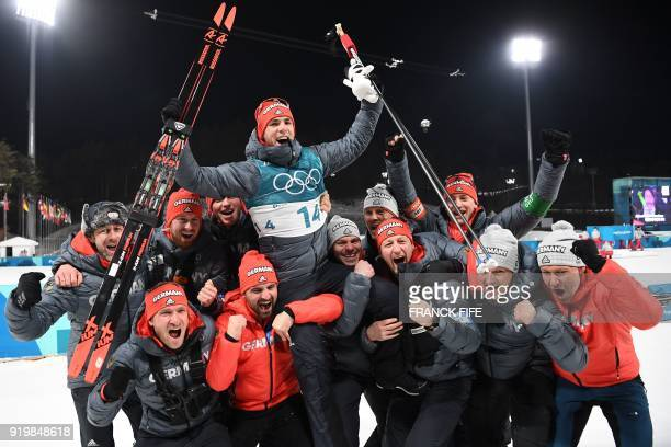 TOPSHOT Silver medallist Germany's Simon Schempp celebrates with his team following the victory ceremony for the men's 15km mass start biathlon event...