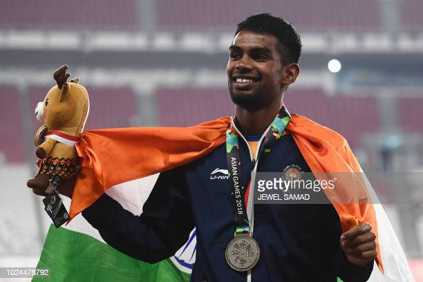Silver medallist India's Dharun Ayyasamy celebrates during the victory ceremony for the men's 400m hurdles athletics event during the 2018 Asian...