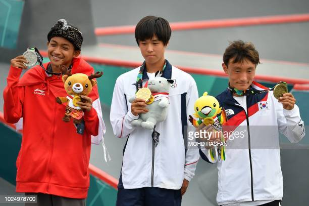Silver medallist Indonesia's Sanggoe Dharma Tanjung gold medallist Japan's Keyaki Ike and bronze medallist South Korea's Eun Juwon pose with their...