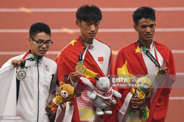 Silver medallist Japan's Toshikazu Yamanishi gold medallist China's Wang Kaihua and bronze medallist China's Jin Xiangqian celebrate during the...