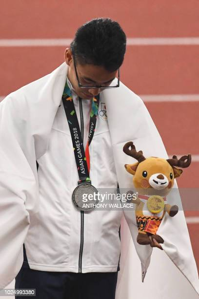 Silver medallist Japan's Toshikazu Yamanishis celebrates during the victory ceremony for the men's 20km race walk athletics event during the 2018...