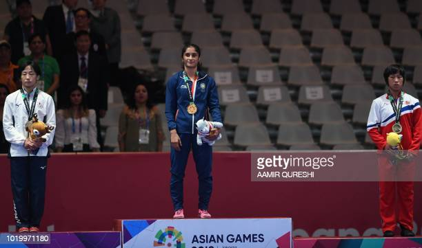 Silver medallist Japan's Yuki Irie gold medallist India's Vinesh Vinesh and bronze medallist North Korea's Kim Son Hyang pose with their medals at...