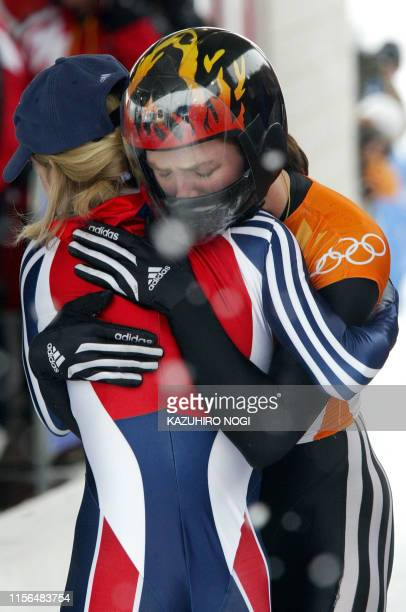 US silver medallist Lea Ann Parsley celebrates with Great Britain's bronze medallist Alex Coomber on the finish line during the women's skeleton...