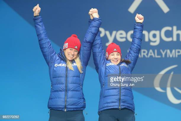 Silver medallist Menna Fitzpatrick of Great Britain and her guide Jennifer Kehoe celebrate on the podium during the medal ceremony for the Alpien...