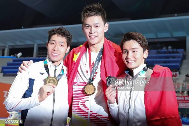 Silver medallist Naito Ehara of Japan, gold medallist Sun Yang of China and bronze medallist Kosuke Hagino of Japan celebrate during the victory...