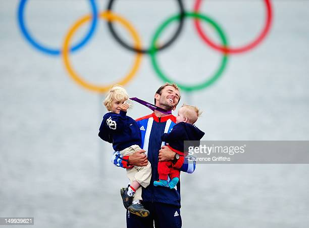 Silver medallist Nick Dempsey of Great Britain celebrates his children ThomasFlynn and Oscar following the Men's RSX Sailing on Day 11 of the London...