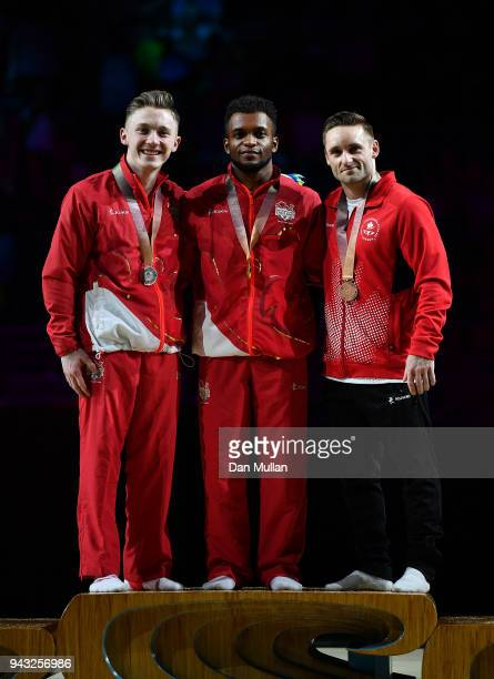 Silver medallist Nile Wilson of England gold medallist Courtney Tulloch of England and bronze medallist Scott Morgan of Canada pose on the podium...