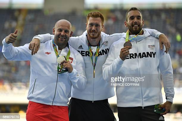 Silver medallist Poland's Piotr Malachowski Gold medallist Germany's Christoph Harting and bronze medallist Germany's Daniel Jasinski celebrate on...