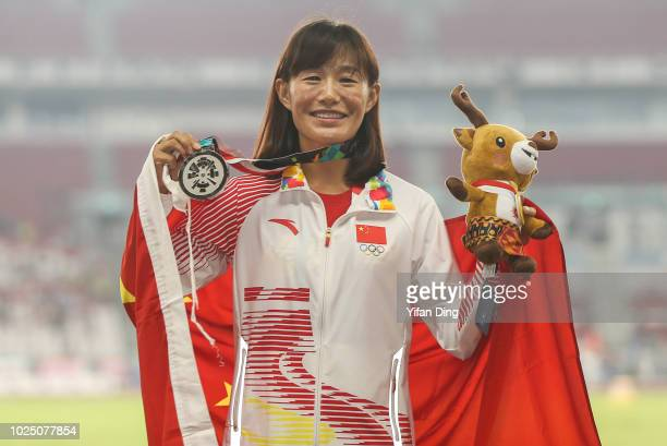 Silver medallist Qieyang Shijie of China of China pose for photo during Athletics WomenÕs 20km Race Walk medal ceremony at GBK Main Stadium on day...