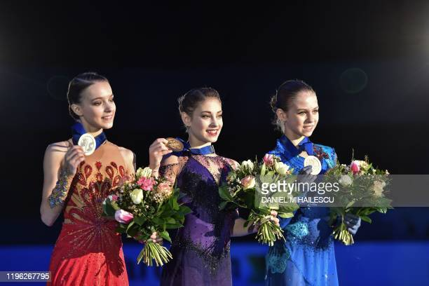 Silver medallist Russia's Anna Shcherbakova gold winner Russia's Alena Kostornaia and bronze medallist Russia's Alexandra Trusova pose on the podium...