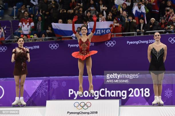 TOPSHOT Silver medallist Russia's Evgenia Medvedeva gold medallist Russia's Alina Zagitova and bronze medallist Canada's Kaetlyn Osmond celebrate on...