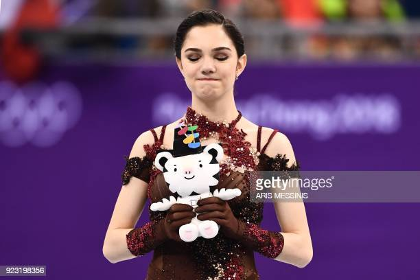 TOPSHOT Silver medallist Russia's Evgenia Medvedeva reacts on the podium during the venue ceremony after the women's single skating free skating of...