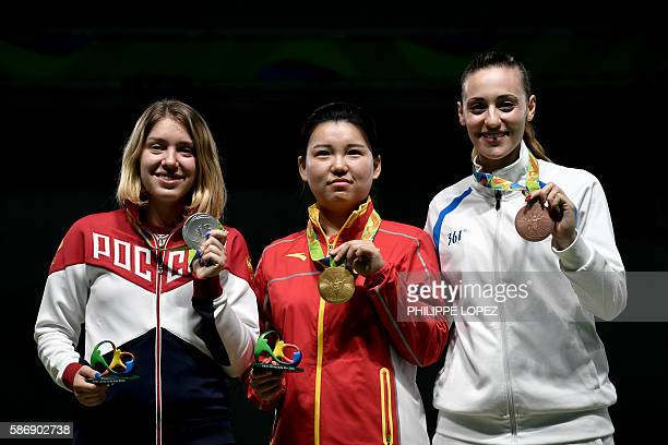 Silver medallist Russia's Vitalina Batsarashkina gold medal winner China's Zhang Mengxue and bronze medallist Greece's Anna Korakaki stand on the...