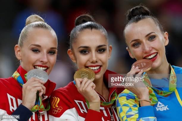 Silver medallist Russia's Yana Kudryavtseva gold medallist Russia's Margarita Mamun and bronze medallist Ukraine's Ganna Rizatdinova pose on the...