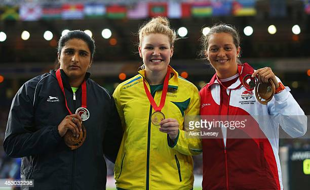 Silver medallist Seema Punia of India gold medallist Dani Samuels of Australia and bronze medallist Jade Lally of England pose on the podium during...