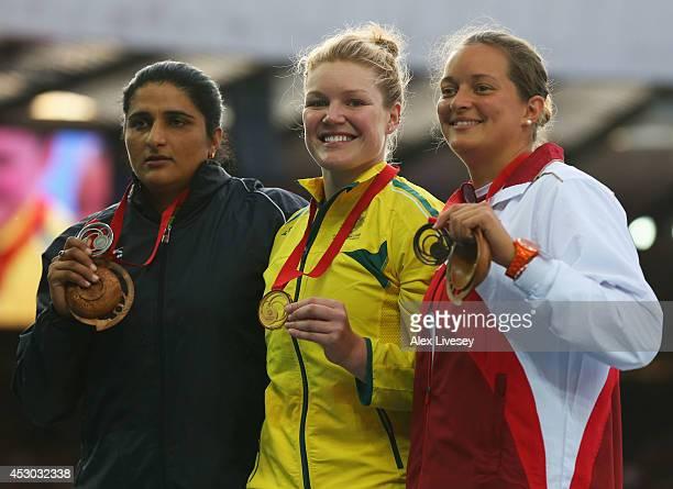 Silver medallist Seema Punia of India gold medallist Dani Samuels of Australia and bronze medallist Jade Lally of England pose on the podium during...