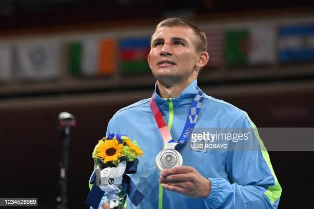 Silver medallist Ukraine's Oleksandr Khyzhniak celebrates on the podium during the medal ceremony for the men's middle boxing final bout during the...