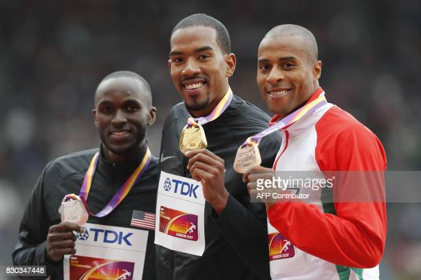 Silver medallist US athlete Will Claye gold medallist US athlete Christian Taylor and bronze medallist Portugal's Nelson Evora pose on the podium...