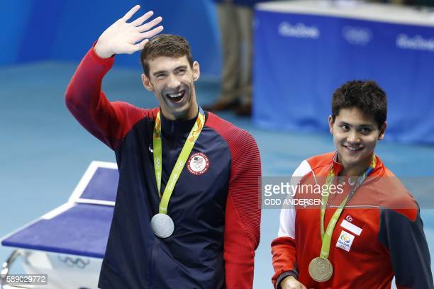 Silver medallist USA's Michael Phelps waves nex to gold medallist Singapore's Schooling Joseph during the medal ceremony of the Men's 100m Butterfly...
