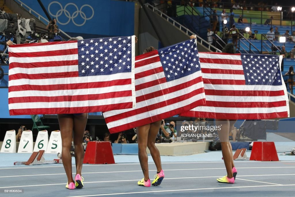 TOPSHOT - (L-R) Silver medallist USA's Nia Ali, gold medallist USA's Brianna Rollins and bronze medallist USA's Kristi Castlin celebrate after the Women's 100m Hurdles Final during the athletics event at the Rio 2016 Olympic Games at the Olympic Stadium in Rio de Janeiro on August 17, 2016. / AFP / Adrian DENNIS